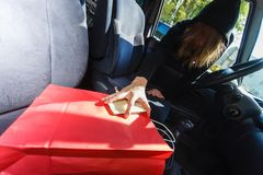 Burglar thief stealing smartphone and bag from car Stock Photos