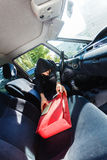 Burglar thief stealing smartphone and bag from car Royalty Free Stock Photography