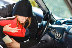 Burglar thief stealing smartphone and bag from car Royalty Free Stock Photos