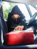 Burglar thief stealing smartphone and bag from car. Anti theft system problem concept. Burglar thief man wearing black clothes breaking into car, stealing stock photo