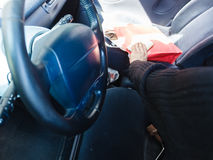 Burglar thief stealing smartphone and bag from car. Anti theft system problem concept. Burglar thief man wearing black clothes breaking into car, stealing stock photos