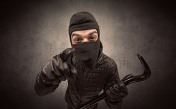 Burglar with tool. Burglar standing in black clothes and balaclava on his head royalty free stock photography