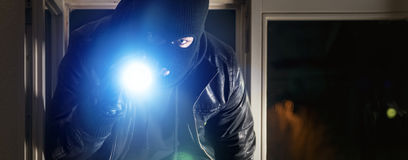 Burglar with torch Stock Photography