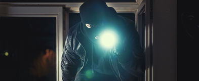 Burglar with torch Stock Image