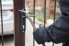 Burglar trying to break the gate with a crowbar. Burglar trying to force a lock using a crowbar royalty free stock image