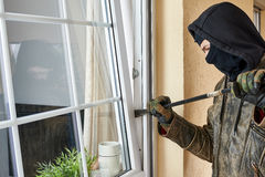Burglar. Trying to break into a house with a crowbar royalty free stock photos