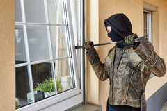 Burglar. Trying to break into a house with a crowbar Royalty Free Stock Photography
