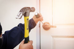 Burglar trying to break into a house with a hammer and Royalty Free Stock Image