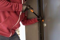 Burglar trying to force a door lock stock image