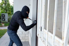 Burglar trying to force a door lock using a crowbar. Burglar trying to force a door lock stock photos