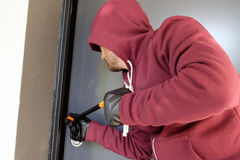 Burglar trying to force a door lock. Using a crowbar royalty free stock images