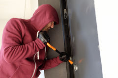 Burglar trying to force a door lock. Using a crowbar stock photo