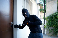 Burglar trying to force a door lock. Using a crowbar royalty free stock photography