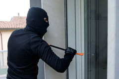 Burglar trying to force a door lock using crowbar. Burglar trying to force a window lock using a crowbar royalty free stock images