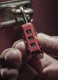 Burglar trying to unlock combination lock Stock Photos