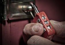 Burglar trying to unlock combination lock Stock Image