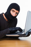 Burglar typing on laptop and looking at camera Stock Photography