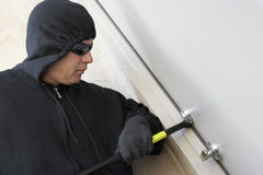 Burglar Using Crowbar To Break Into House. Burglar with crowbar trying to break into a house royalty free stock photography