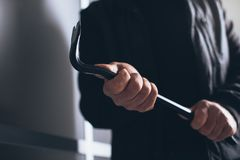 Burglar using a crowbar to break into a house. Dangerous burglar using a crowbar to break into a house late at night, home safety concept stock photography