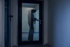 Burglar Using Crowbar To Open Glass Door. Full length of burglar using crowbar to open glass door at night royalty free stock photo