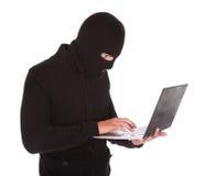 Burglar using laptop stock photography