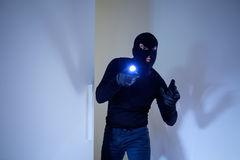 Burglar wearing a balaclava. Holding a flashlight royalty free stock photo