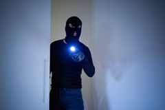 Burglar wearing a balaclava holding a flashlight Royalty Free Stock Photos