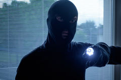 Burglar wearing a balaclava holding a flashlight. In the night royalty free stock images