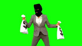 Burglar wearing balaclava and holding money bags on green screen Royalty Free Stock Photography