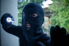 Burglar wearing a balaclava l. Ooking through the house window royalty free stock photos
