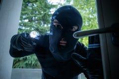 Burglar wearing a balaclava. Looking through the house window stock photo