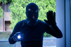 Burglar wearing a balaclava looking through the house window. Burglar wearing a balaclava holding a flashlight in the night royalty free stock photos