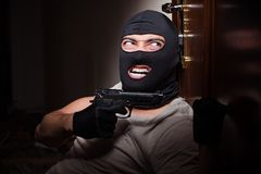 The burglar wearing balaclava mask at crime scene. Burglar wearing balaclava mask at crime scene Royalty Free Stock Images