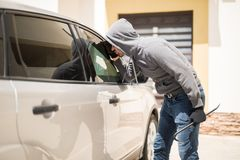 Burglar trying to steal from a car Royalty Free Stock Photo