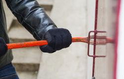 Burglar wearing leather coat breaking in a house Stock Photography