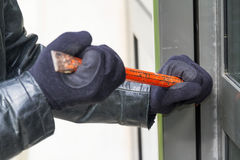 Burglar wearing leather coat breaking in a house. Burglar trying to break into a house with a crowbar Stock Image