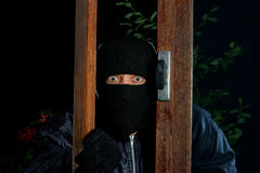 Burglar window four. A burglar trying to enter through a window stock photo