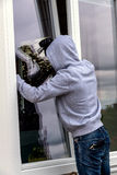 Burglar at a window. A burglar trying to break in an open window with a crowbar royalty free stock photos