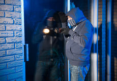 Burglar at work. A burglar is looking through the window of a house Stock Photo