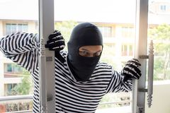Burglarize try to break into the room to steal. Criminal concept/A thief in a black mask breaks apartment window Stock Photography