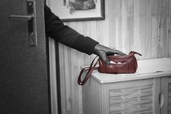 Burglary. Thief breaking into doors and stealing a handbag Stock Image