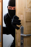 Burglary crime - burglar opening a door Royalty Free Stock Images