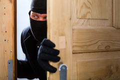 Burglary crime - burglar opening a door Royalty Free Stock Images