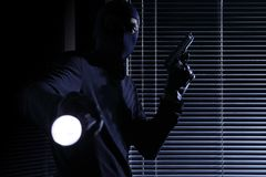Burglary and robbery. skillful professional masked burglar wears a balaclava, holding a gun and torch and breaking into the house. On black door window stock photography