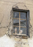 BURGO DE OSMA, SORIA, SPAIN – JULY, 1978. Two elderly women seen through the window of his ruinous house, what happens on the street of a Castilian village on Stock Images