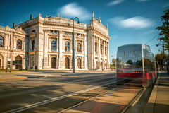 Burgtheater building in Vienna. Burgtheater building with red tram in Vienna. Long exposure image technic with blurred cars and clouds Royalty Free Stock Photos