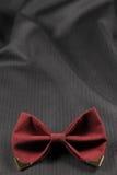 Burgundy łęku krawat przy tkankowym tłem fotografia royalty free