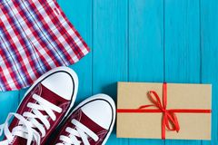 Burgundy πάνινα παπούτσια, ελεγμένα πουκάμισο και κιβώτιο δώρων στο φωτεινό turquo Στοκ φωτογραφία με δικαίωμα ελεύθερης χρήσης