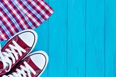 Burgundy πάνινα παπούτσια και ελεγμένο πουκάμισο στο φωτεινό τυρκουάζ backgr Στοκ Εικόνα