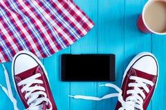 Burgundy πάνινα παπούτσια, κινητό τηλέφωνο, καφές, ελεγμένο πουκάμισο σε φωτεινό Στοκ Εικόνες